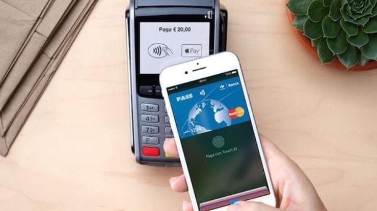 Uma compra sendo paga por um smartphone. Com o celular em primeiro plano, e a máquina de cartão atrás; a compra está sendo paga com o Apple Pay.