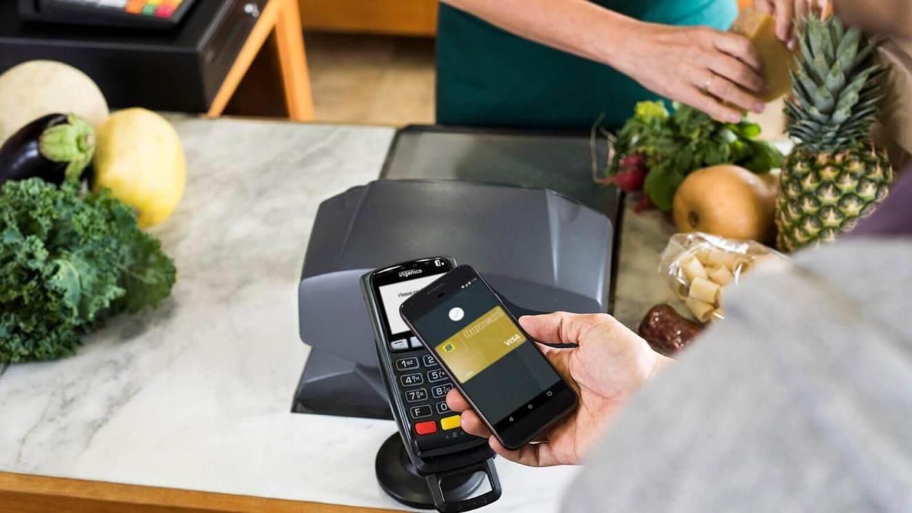 Uma pessoa prestes a pagar uma compra por um smartphone, e uma máquian de cartão em segundo plano.
