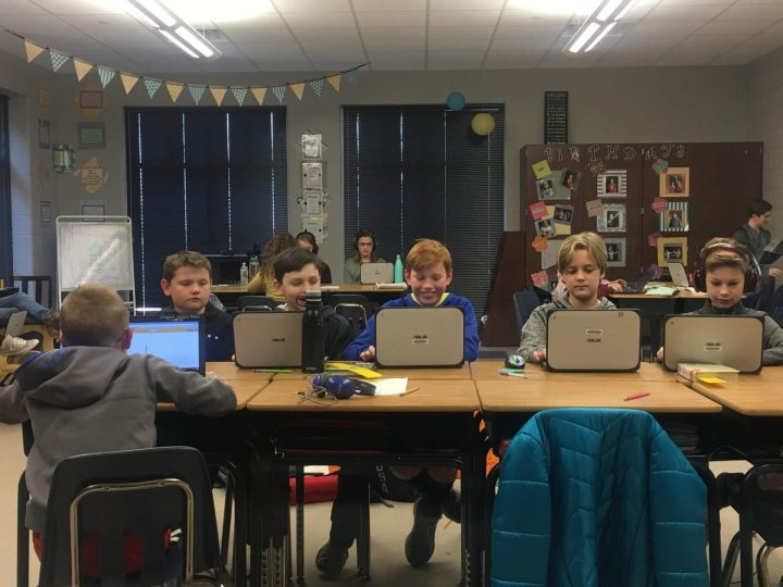 Crianças usam notebook em escola