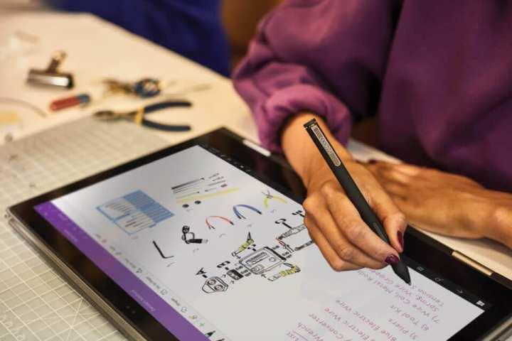Mulher desenhando na tela de um tablet com OneNote, utilizando uma caneta
