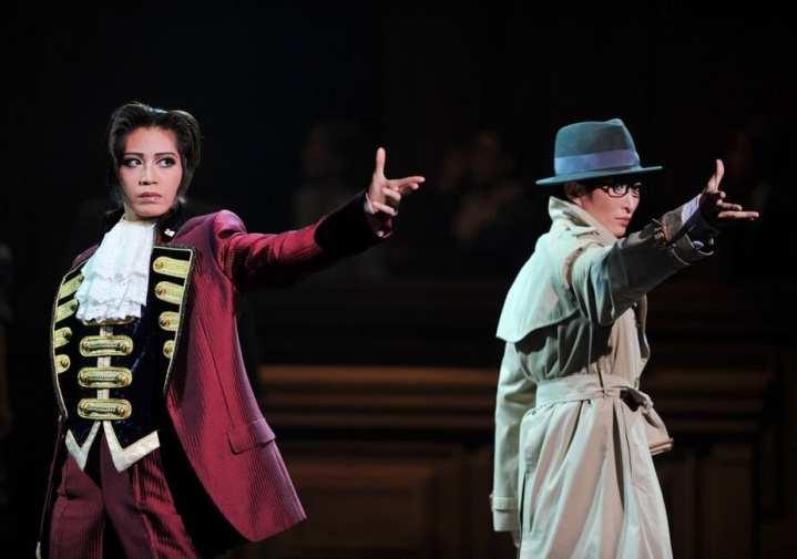 Foto mostra duas mulheres com cosplay de personagens de Phoenix Wright durante o musical, um é o culprit, o culpado, e o outro é o Miles Edgeworth