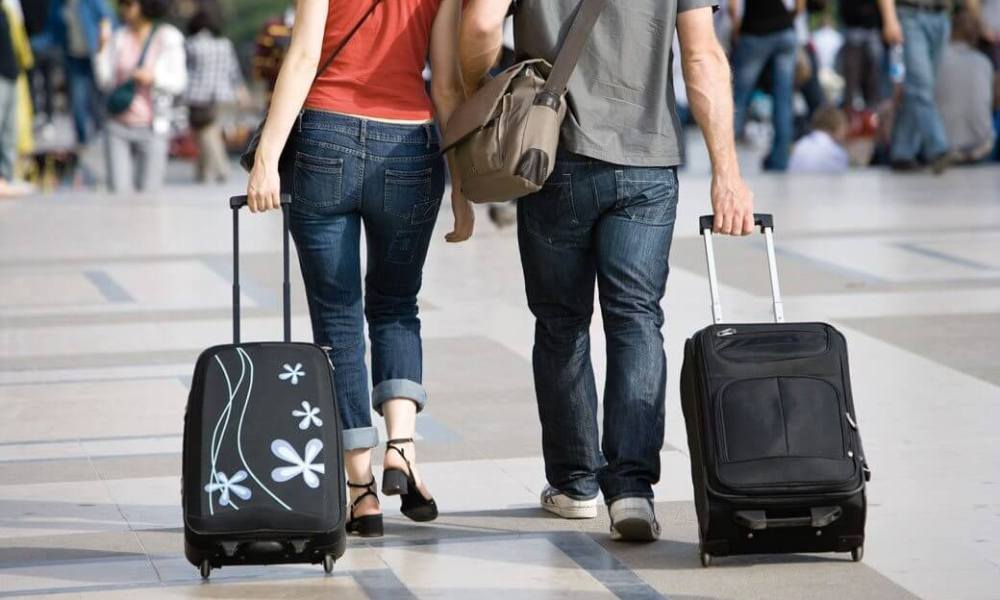 C84NJ8 Couple walking outdoors with rolling luggage