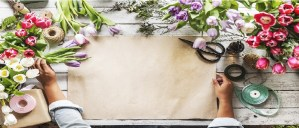 hand with paper and flowers on the table