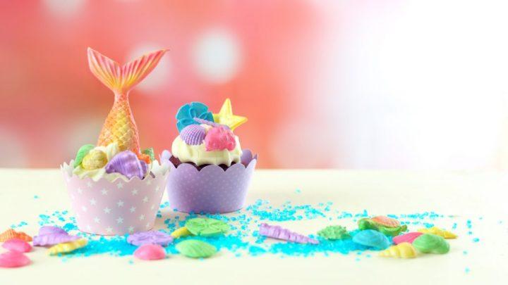 Cupcakes temáticos de sirena con colas de colores brillantes, conchas y adornos de criaturas marinas para la fiesta de cumpleaños de sirenas para niños