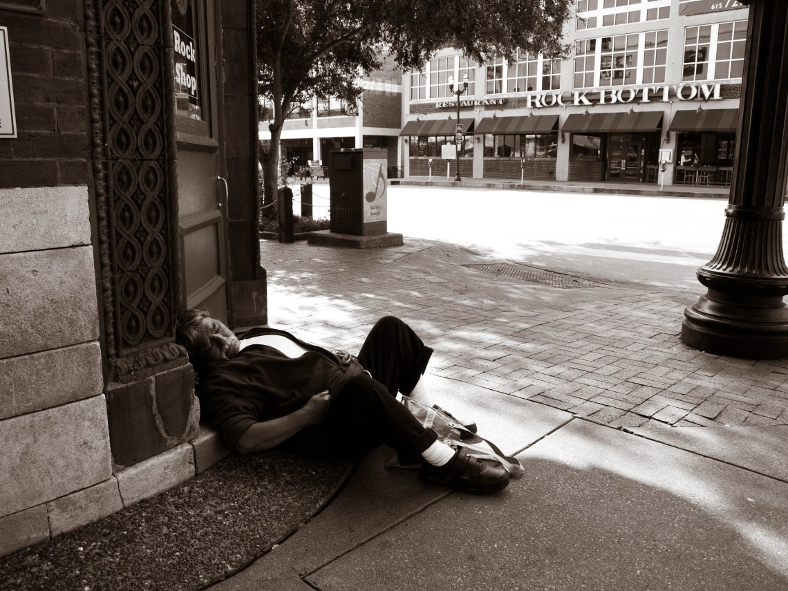 Homeless Man Sleeping at the Corner of Broadway and 2nd Avenue in Downtown Nashville, Tennessee