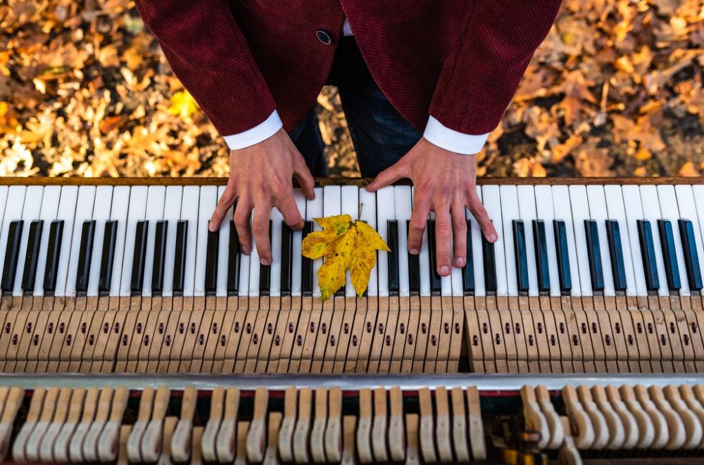 handen die pianospelen op een piano waar een geel herfstblad op ligt
