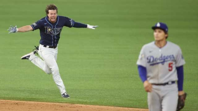 Tampa Bay Rays right fielder Brett Phillips (14) celebrates after driving in the winning run as Los Angeles Dodgers shortstop Corey Seager (5) looks on during the ninth inning of game four