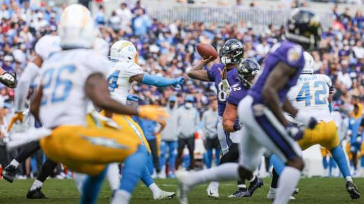Oct 17, 2021; Baltimore, Maryland, USA; Baltimore Ravens quarterback Lamar Jackson (8) throws a touchdown pass as Los Angeles Chargers outside linebacker Kyzir White (44) defends during the second half at M&T Bank Stadium. Mandatory Credit: Vincent Carchietta-USA TODAY Sports