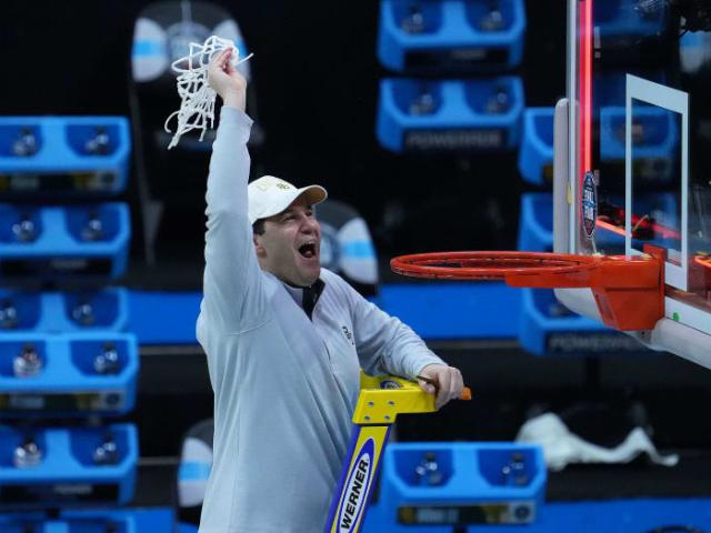 Scott Drew holds up the net after Baylor's win
