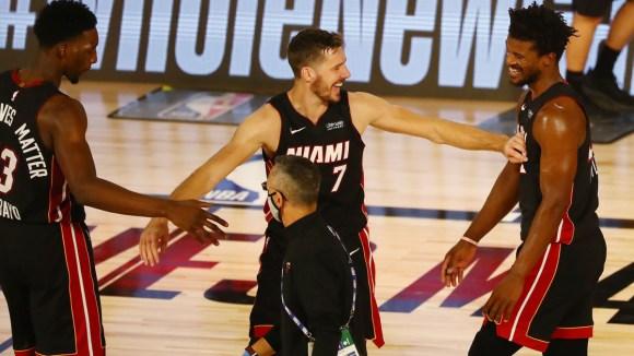 Miami Heat forward Jimmy Butler celebrates with guard Goran Dragic and forward Bam Adebayo after defeating the Milwaukee Bucks