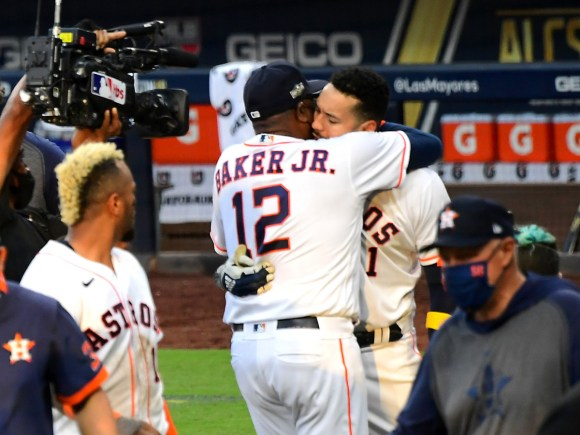 Oct 15, 2020; San Diego, California, USA; Houston Astros shortstop Carlos Correa (1) is embraced by manager Dusty Baker (12) after hitting a walk off solo home run in the ninth inning of game five of the 2020 ALCS to defeat the Tampa Bay Rays at Petco Park.
