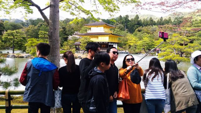 Chinese tourists visiting the Golden Temple in Kyoto, Japan.