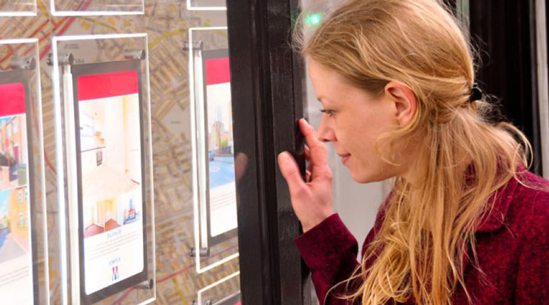 Sian looking at letting agent window
