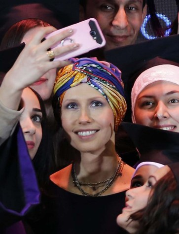 Syria's First Lady Asma al-Assad (C) poses for a picture during a graduation ceremony of future teachers of a Syrian Organisation for Persons with Disabilities, in Damascus on December 3, 2018. - The Syrian president's wife is currently undergoing treatment for breast cancer, the presidency said earlier this year. (Photo by LOUAI BESHARA / AFP)