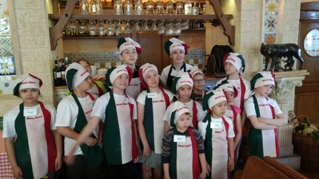 The children in their aprons and chef's hats pose for a group picture.