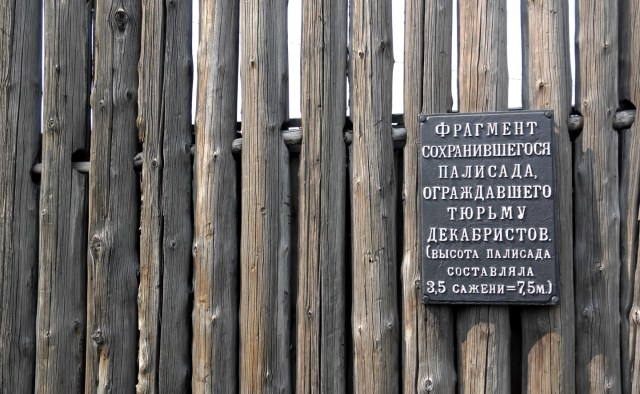 log stockade with descriptive sign in Russian