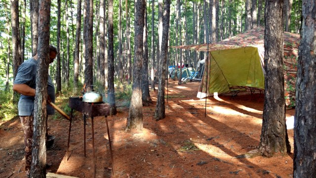 campground with kettle heating on grill, kitchen tent, neighbor tenstie in the background