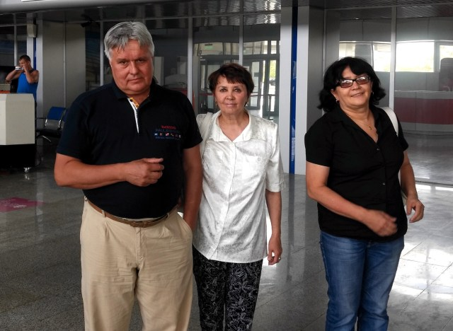 three adults standing for a photo in an airport