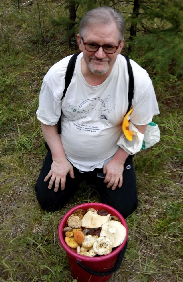 a man crouches behind a bucket of mushrooms