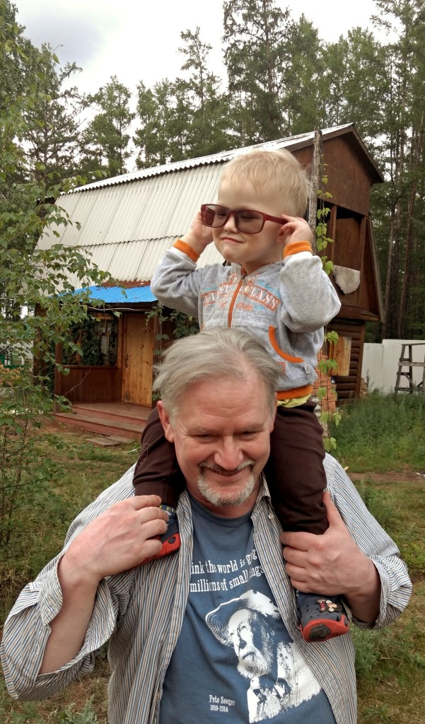 boy on the shoulders of a man and trying on his glasses
