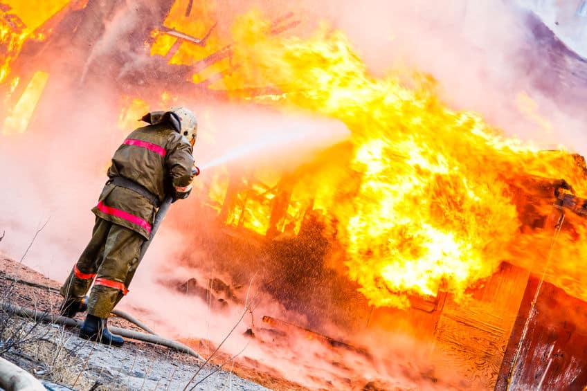 47767605 – fireman extinguishes a fire in an old wooden house
