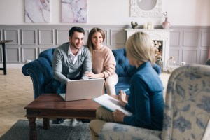 A smiling young couple sitting in their living room with a woman with a Behaviour Therapist having a parent/caregiver coaching session by Side by Side Therapy.