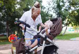 Woman walking with a baby in a stroller at the park during a respite services in Toronto session.