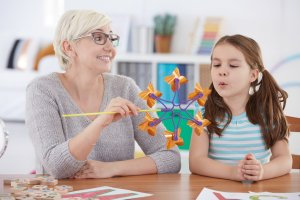 Child and speech therapist working on blowing activity during speech therapy in Toronto