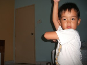 Young Boy stretching his arm across his body during an occupational therapy in Toronto session.