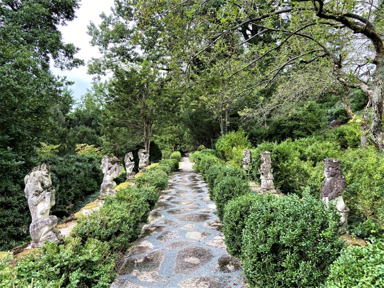 Stone statues along a rustic path look like large chess pieces.