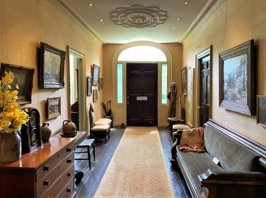 The house's wide center hallway served as a display area and gallery for artists' works as well as a place to relax.