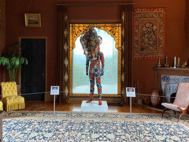 """Nick Cave's Soundsuit, 2006–2012, part of """"Cross Pollination,"""" has detailed beaded flowers and is called """"part costume, part sculpture, part armor"""" in the exhibition."""
