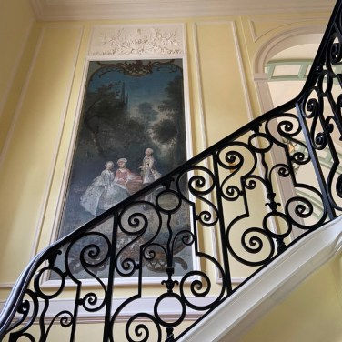 Decorating the staircase leading to the Gallery and other rooms are several 18th-century-style paintings set into wall panels.