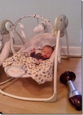 baby sleeping in swing with hairdryer