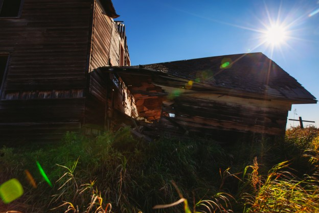 Exterior of an abandoned house mid-autumn morning in rural Alberta, deserted structures. Copy space horizontal.