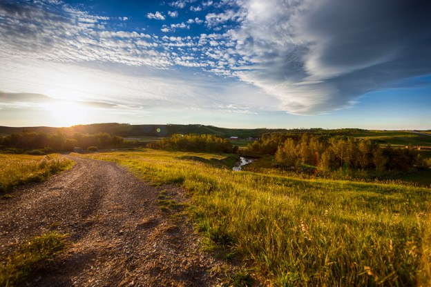 Late summer sunrise over a rural Alberta farmland with a gravel dirt road, Southern Alberta landscape.