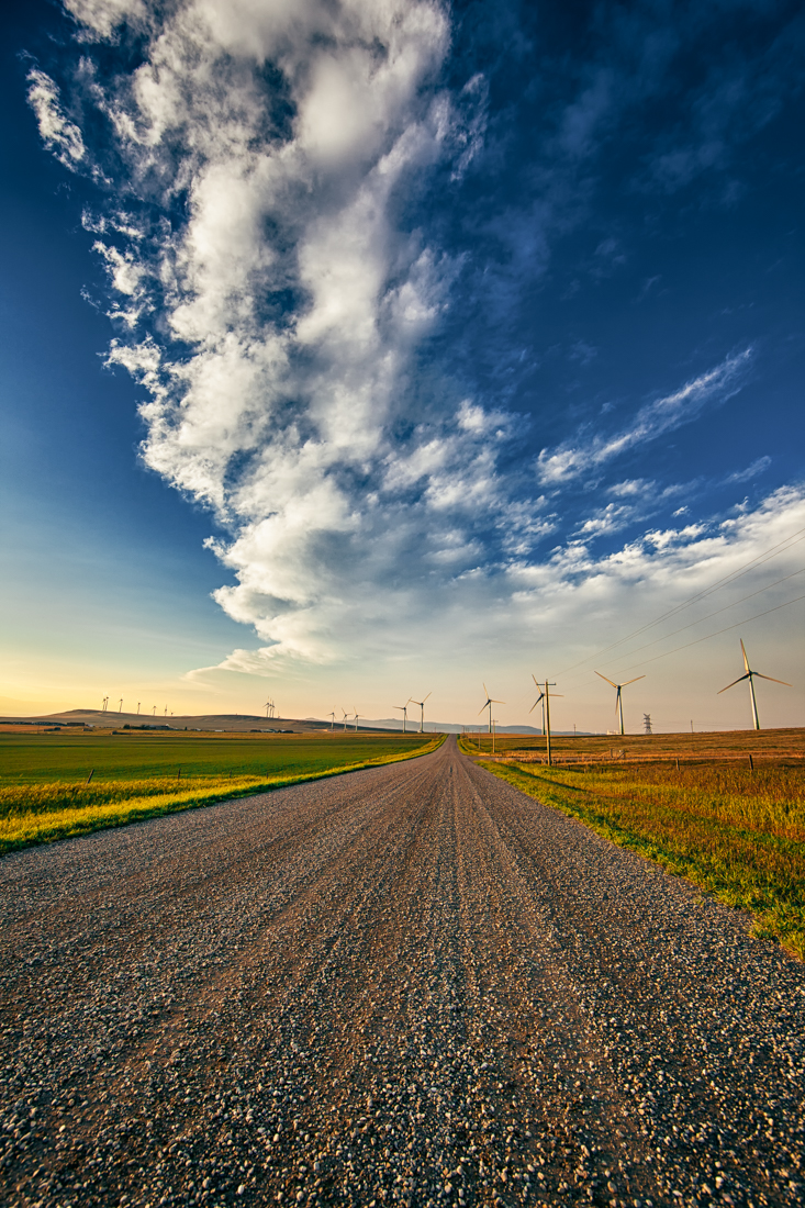 Pincher Creek wind farm with a gravel dirt road down the middle during a late summer sunset against a Canadian Rockies backdrop, Alberta landscape. Copy space vertical