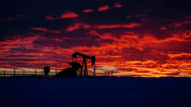 Working pumpjack during a mid-winter sunrise, fine art oil and gas rural Alberta landscape.