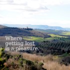 Image of a hillside with a the convent Santa Anna In Camprena , Tuscany, in the forground with the caption Where Getting Lost Is A Pleasure.