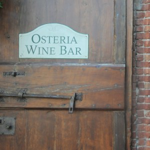Image of a dark wood tuscan door with hand made iron bolt and a sign reading Osteria Wine Bar
