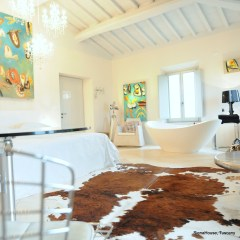 Image of the 'Cortona' room showing free standing designer tub large bed and cow hide rug and art by interior designer and artist Amanda Helen Atkins