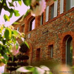 image showing a red brick and stone front of a restored tuscan farm house framed with roses and with romantic feeling