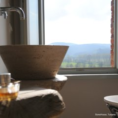 Image of a stone vessel sink in marble with rolling hills view the Siena room at Siena House