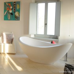 Image of a large white free standing tub with two rubber ducks perched on the rim. Shaft of sunlight diagonally across the white room.