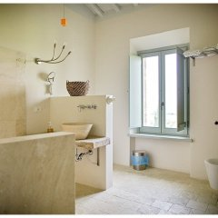 Image of one of the bathrooms in a modernised tuscany country property showing stone floor and walls in whites