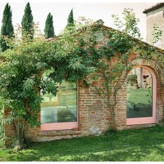 image showing a rose covered pig sty in a tuscan country farm house with cypress trees in the back ground and grass in the foreground