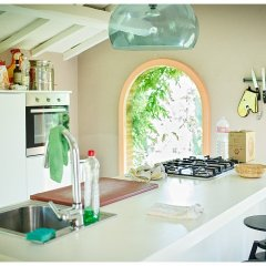 image showing a modern kitchen in a small stable in the garden of a restored tuscan hill top villa showing white doors and surfaces bar stools in black starke lamp magnetic kniife rack and oven in the foreground sink and tap