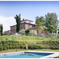 Tuscan villa on hill with pool and cypress trees