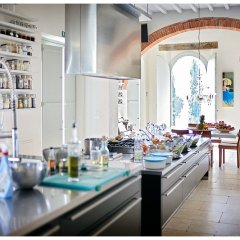 Image showing a fully equipped modern free standing bar kitchen in a large open plan socializing zone in a modernised tuscan farmhouse with red brick arch and dingin area in the background and cypress trees visible from the large windows an artist designed interior by amanda helen atkins