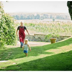 Image showing the owner of a boutique bed and breakfast in the garden of his villa with his young son, showing a summers day in the garden with good light green grass a little boy walking and a man behind him in a bakers apron the wall surrounding the property and vineyards beyond the wall at right, at left a stone path and an outbuilding covered in honeysuckle